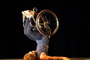 Dancer, Alice Sheppard on stage using a wheelchair.  Click link to magnify and go to image source.