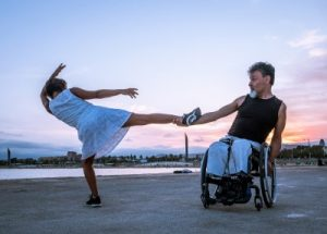 Barcelona, Catalonia / Spain - August 2018: A man using a wheelchair dances with a woman on the beach 2.  Click link to magnify and go to image source.