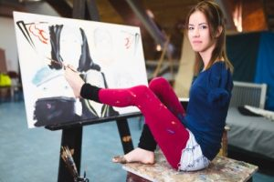 Young artist with a disability painting incredible scenes in attic by holding paintbrush in her toes.  Click link to magnify and go to image source.