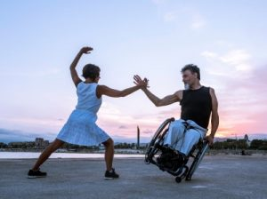 2 dancers in strong pose, one using a wheelchair and one, not.  Link to image source.  Click to magnify image size.