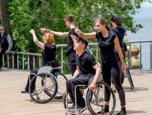 Group of dancers performing in the open air, som are using wheelchairs and some are not.  Click to magnify picture and go to image source.